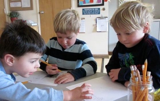 Three four year old boys writing numbers
