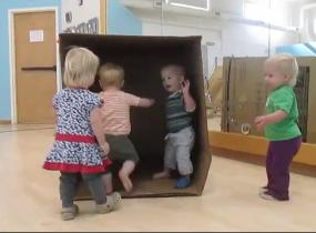 Four toddlers enjoy running in and out of a life size box